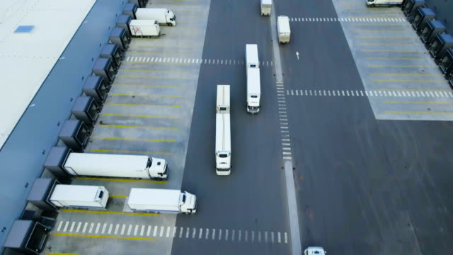 aerial shot of truck with attached semi trailer leaving industrial warehouse/ storage building/ loading area where many trucks are load/ unload merchandise. - тягач с полуприцепом стоковые видео и кадры b-roll