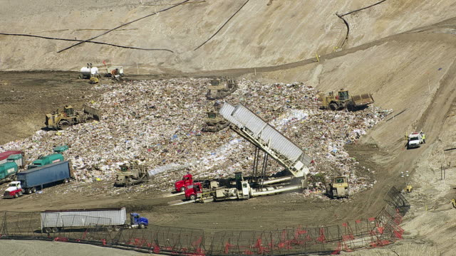 Aerial shot of trucks and tractors working in landfill video