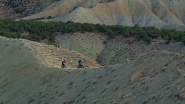aerial shot of two mountain bikers riding along a ridge on 18 road in fruita, colorado - bike tire tracks video stock e b–roll