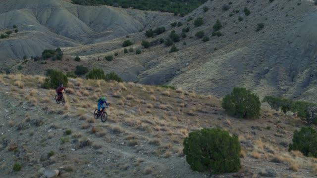 aerial shot of two mountain bikers riding along a ridge on 18 roadin fruita, colorado - bike tire tracks video stock e b–roll