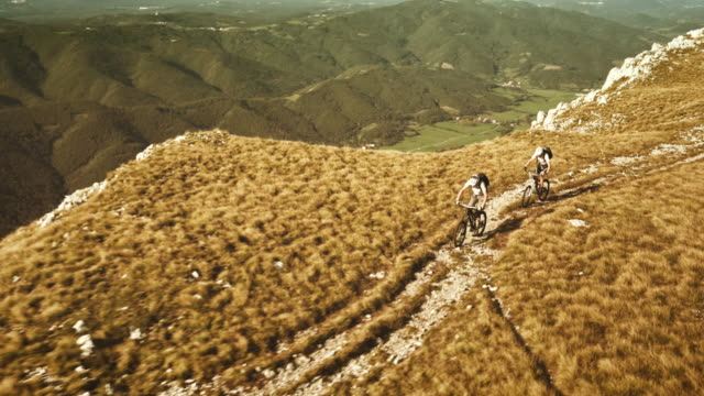 Aerial shot of two mountain bikers riding the ridge video