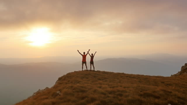 Aerial shot of two runners reaching the top at sunset video