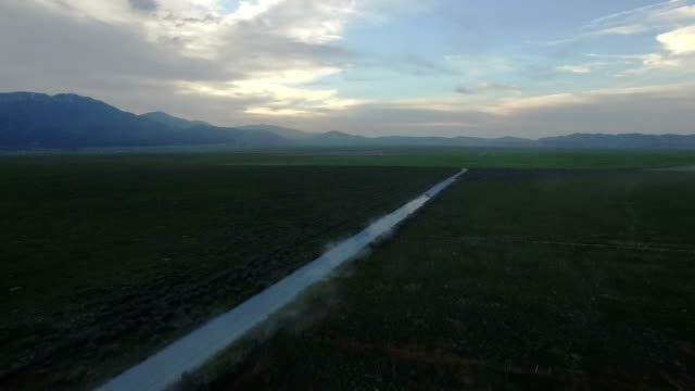 Aerial shot of vehicle driving at sunset on dirt road video