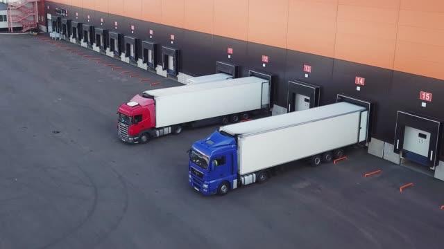 積み下ろしドックの倉庫の空中ショット トラックのトレーラーの負荷または降ろす位置 - トラック点の映像素材/bロール