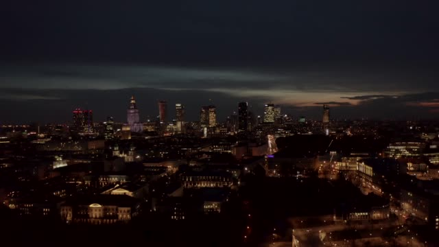 4K. Aerial shot of Warsaw city metropolis skyline at night. Spectacular aerial view of skyscraper city buildings at night