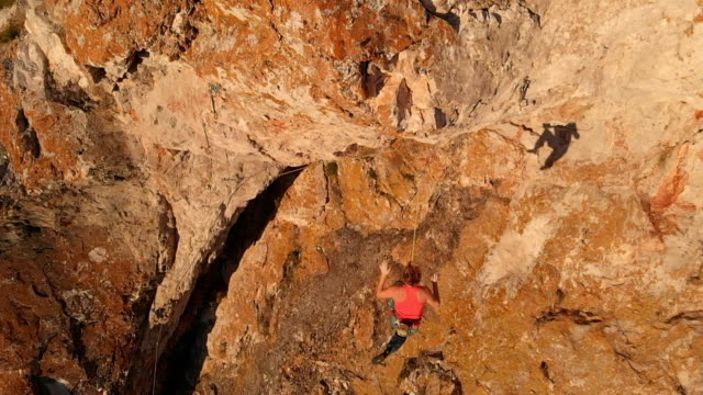 Aerial shot of young brave woman climber climbs the rock breaks, falls down and hangs on a safety rope.