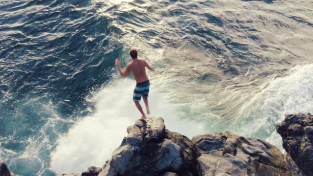 4k aerial shot of young man jumping off ocean sea cliff into sunset. - cliffs stock videos & royalty-free footage