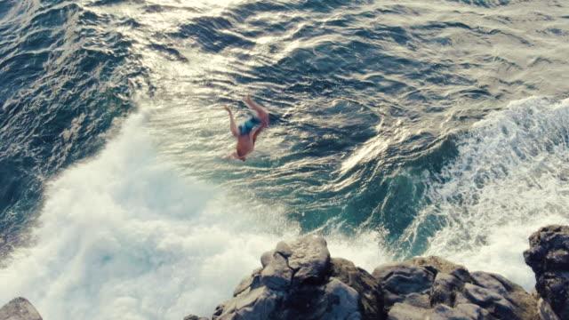 4k 年輕男子從海崖跳入日落的空中鏡頭。 - 懸崖 個影片檔及 b 捲影像
