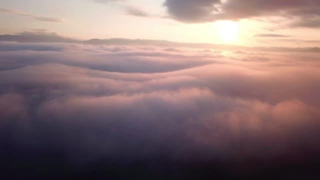 antenn skott på molnen ovan molnen med soluppgång tid, drömmer och inspiration koncept - earth from space bildbanksvideor och videomaterial från bakom kulisserna