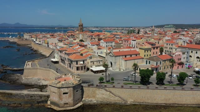 aerial shot over alghero old town, cityscape view on a beautiful day with harbor and open sea in view. alghero, italy. panoramic aerial view of alghero, sardinia, italy. - sardegna video stock e b–roll