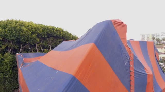 Aerial shot over house covered with tent for fumigation and neighborhood video