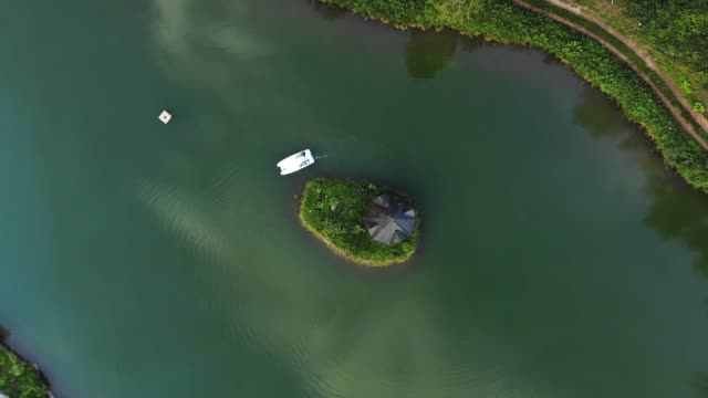 Aerial shot, summer wooden house on isolated island in lake in green forest video