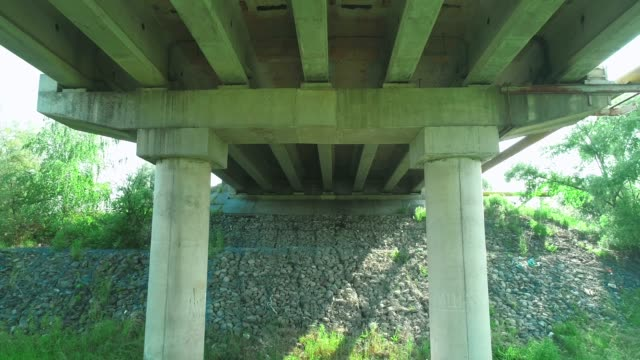Aerial shot under the bridge symmetry with rock basis. 4K.