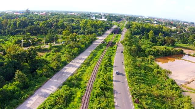 vídeos de stock e filmes b-roll de fotografia aérea ver caminhos  de  ferro com estrada em verde apresentado - reto descrição física