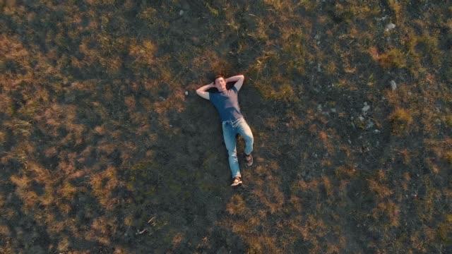 aerial shot young man lying down and resting - leżeć filmów i materiałów b-roll