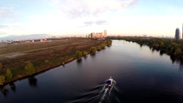 Aerial shots of pleasure boat on the Moskva River at Strogino district of Moscow, Russia. Boat navigate on the Moscow river. Sunrise sunset. Alie parusa buildings video