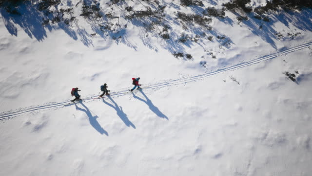 Aerial Ski tourers skiing along a path across the mountain video