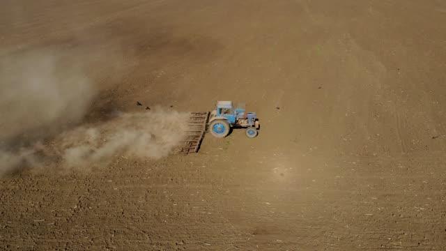 Aerial glidande skott jordbrukare på blå traktor plöjning dammig torra jord. Jordbruksnäringen på våren video