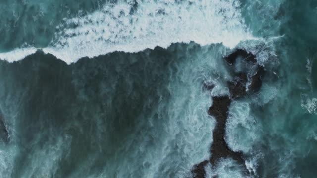 vídeos y material grabado en eventos de stock de toma aérea lenta de olas precipitándose hacia la costa rocosa - roca