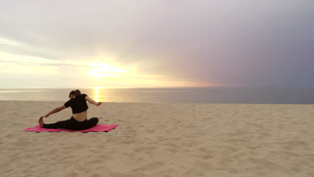 Aerial slow motion video Women playing yoga On the beach