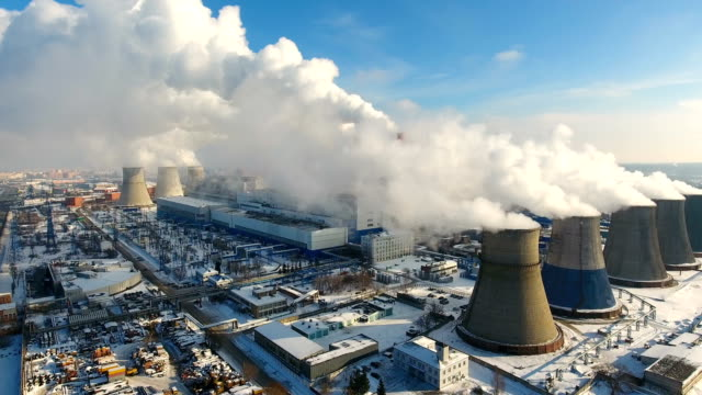 Aerial. Smoke and steam from industrial power plant. Contamination, pollution, global warming concept.