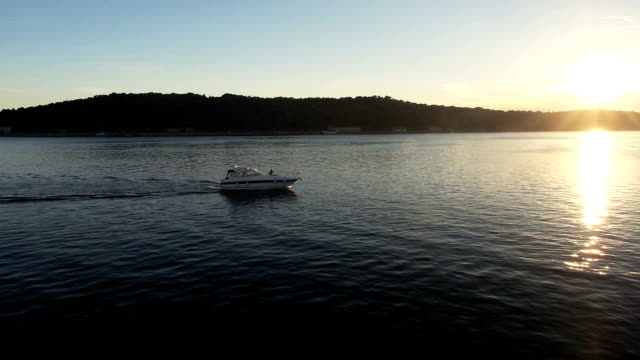 aerial: speedboat slowly sails on water at sunset - port wine stock videos & royalty-free footage