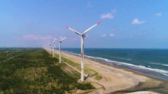 aerial - sunny day's wind power plant and sea - энергия ветра стоковые видео и кадры b-roll