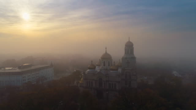 vídeos de stock, filmes e b-roll de vista aérea do nascer do sol sobre a catedral da assunção, em varna, bulgária - multicóptero