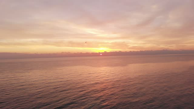 Aerial sunset over the sea with wonderful lights and  gorgeous pastel colored pink and orange sky