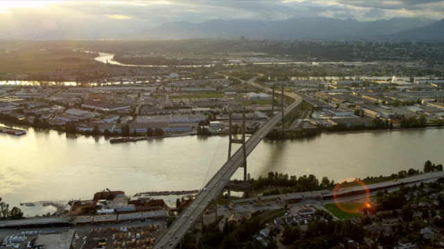 Aerial sunset view Alex Fraser Bridge, Vancouver Aerial sunset sun flare view Alex Fraser Bridge on Annacis Island a cabled stayed bridge Fraser River connects New Westminster with North Delta Vancouver, BC, Canada fraser river stock videos & royalty-free footage
