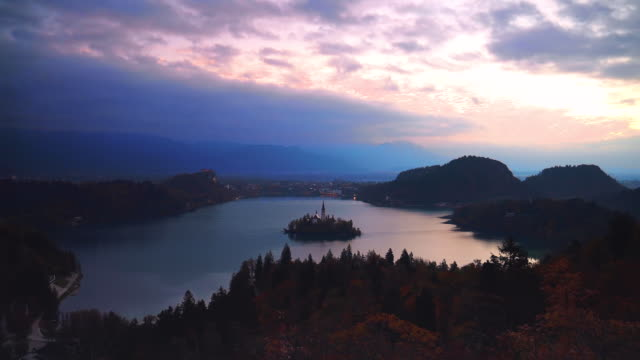 Aerial sunset view of lake Bled and church on small island in Slovenia, Alps mountain as background