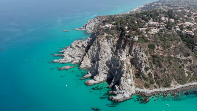 aerial survey from a drone over mediterranean blue sea and rocks italy calabria - video di tropea video stock e b–roll
