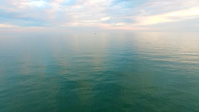 Aerial survey of the water surface of the sea under the cloudy sky. Aerial survey of the water surface of the sea under a cloudy sky and a small ship on . 天の川 stock videos & royalty-free footage