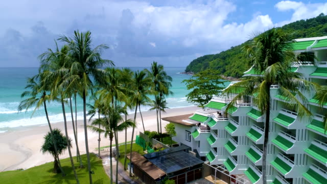 Aerial: Take off on a palm beach with white sand and green grass. Hotel resort. video