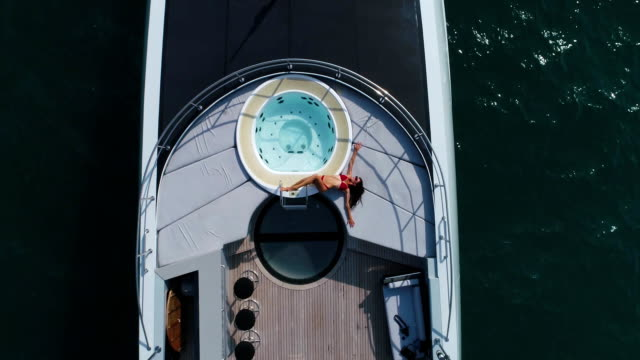 Aerial: The girl lies and sunbathes on the deck of the yacht near the hot tub.