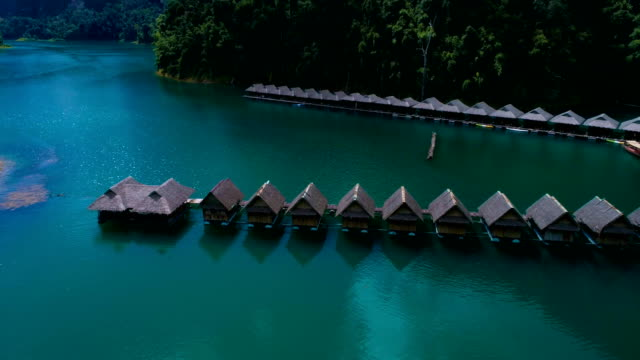 Aerial: The hostel on the lake with thatched roofs houses on the water. video