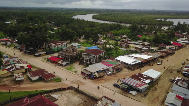 aerial third world country street with river and lush jungle in background - liberia video stock e b–roll