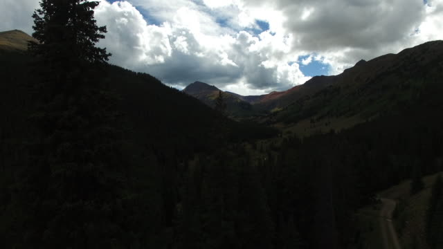 Aerial Through Trees Toward Mountain Range With Valley And River In Foreground