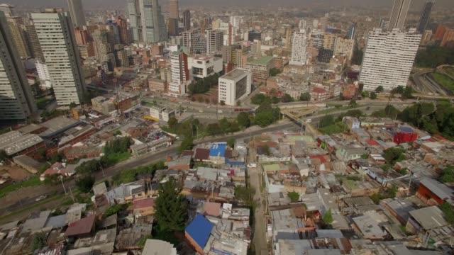 vídeos de stock, filmes e b-roll de inclinação aérea acima de aproximar o escritório e os edifícios residenciais da baixa de bogotá sobre a cidade shanty - característica arquitetônica