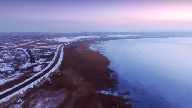 Aerial time-lapse video of suburban road and frozen lake video