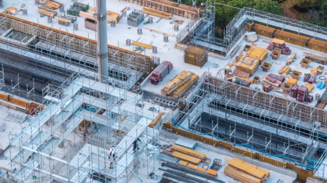 aerial time-lapse: working in construction site in tokyo - industria edile video stock e b–roll