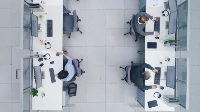 vidéos et rushes de aérienne top down drone shot de big busy bureau corporatif avec des lignes de remorquage hors hommes d'affaires et femmes d'affaires travaillant sur des ordinateurs de bureau. bureau de l'espace ouvert lumineux avec les hommes d'affaires et les ve - dessus