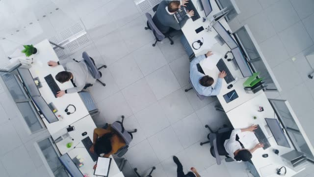 vídeos de stock e filmes b-roll de aerial top down drone shot of big busy corporate office with tow rows off businessmen and businesswomen working on desktop computers. bright open space office with businesspeople and salespeople - acima