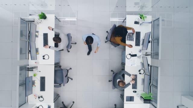 aerial uppifrån drone shot av stora upptagen corporate office med två rader av affärs män och affärs kvinnor arbetar på station ära datorer. ljust open space office med företagare och säljare - direkt ovanför bildbanksvideor och videomaterial från bakom kulisserna