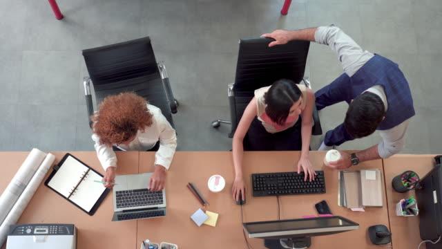 aerial top down shot of busy corporate modern office with rows off multi-ethnic businesswomen working on desktop computer and laptop, manager diskutieren und bestimmen kollegen arbeit. konzept der führung und des unternehmensgeschäfts. - blickwinkel der aufnahme stock-videos und b-roll-filmmaterial