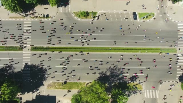 aerial top down shot of city road crowded by cyclists during bicycle competition - campionato video stock e b–roll