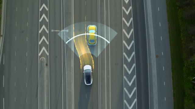 vidéos et rushes de vue de haut en bas aérienne : voiture autonome d'autoconduite se déplaçant par la ville, dépassant d'autres véhicules. concept de visualisation de numérisation animée : l'intelligence artificielle digitalise et analyse la route à suivre - véhicule terrestre