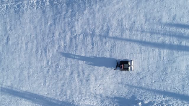 Aerial top down view of a snowcat or snow groomer on a ski resort slope in winter