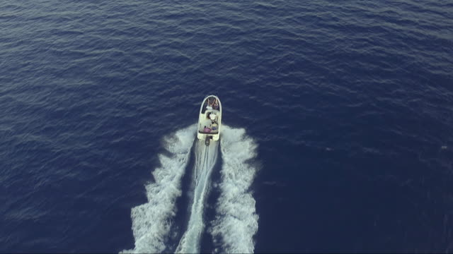 Aerial - Top down view of catching luxury motor boat racing on the water with family on it Aerial - Top down view from drone of catching luxury motor boat racing on the water with four people on it recreational boat stock videos & royalty-free footage