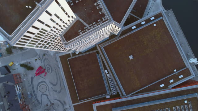 Aerial top down view of moderna skyscraper office buildings. Drone shot flying over rooftop high rise building
